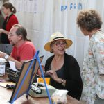 Joan Hawkins speaks with Suzanne Schwibs as she writes on-demand poems for visitors to the booth.
