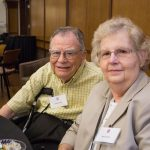 An alumni and his wife smile for a photo