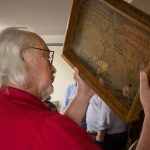 An alumni hold up a signed wooden desk drawer.