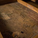 A wooden desk drawer covered with signatures