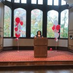 Jamie Zega stands at the podium in President's Hall