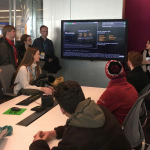 Meg Ely gives a presentation to students using a screen in the Bloomberg office