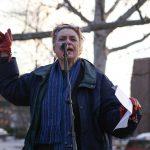 Media School associate professor Joan Hawkins stands a reads a poem into a microphone in Dunn Meadow