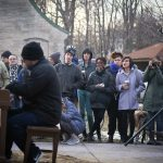 A crowd watches a man playing a piano