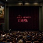 "The IU Cinema curtain, with the words ""Indian University Cinema"" projected."