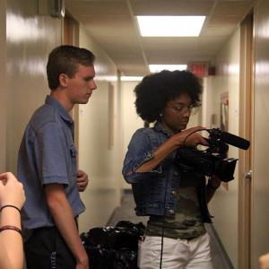 A student uses a camera while two others look on