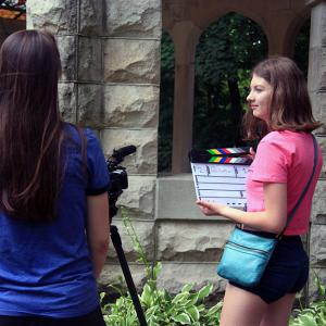 A student holding a slate speaks with two others setting up the camera