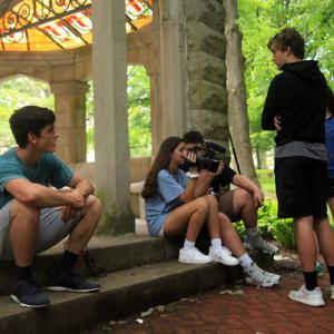 Students sit and chat at the steps of the Rose Well House