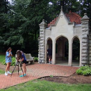 Two students set up a camera in front of the Rose Well house