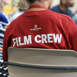 """A student wearing a T-shirt that says """"Film Crew"""" on the back."""