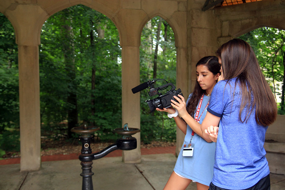 Two students look at their camera footage in the Rose Well house