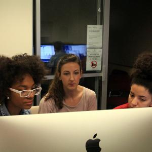 Three students work together to edit footage