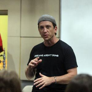 """John Armstrong, wearing a shirt that says """"Dreams aren't dumb"""" speaks to students."""