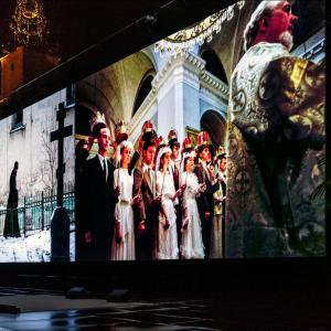 Images of a cemetery and an orthodox church service are projected onto a giant screen at Visa Pour l'Image in Perpignan, France.