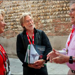Emeritus professor Steve Raymer (right), talks with Emmanuel Sautai of Beaune, France, and his wife outside at the Visa Pour l'Image international photojournalism festival. Sautai, holding Raymer's new book, edited the multimedia show of Raymer's pictures.