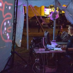 Big Tent creator Robin Cox monitors the performance on a computer outside of the tent