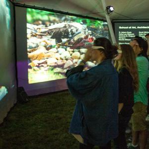 Big Tent visitors watch the content through 3-D glasses.