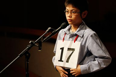 A contestant of the spelling bee stands at a microphone