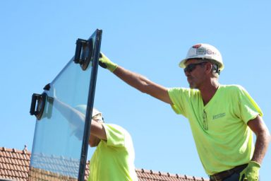 Two workers prop up a glass panel