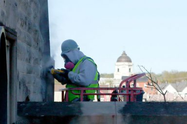 A construction worker working on an external wall of Franklin Hall