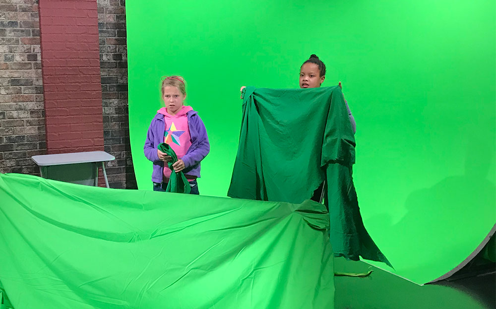 Two young girls stand before a green screen