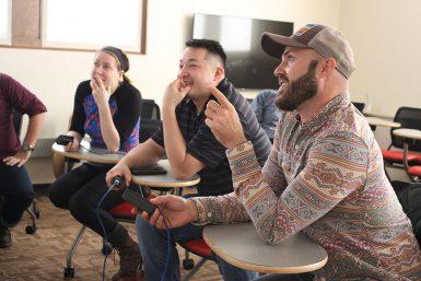 INPA judges Jessica Phelps, Corey Perrine and Dustin Alton Strupp analyze student work. (Kristen Braselton   The Media School)