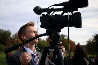 Andrew Lamparski positions a camera in Dunn Meadow