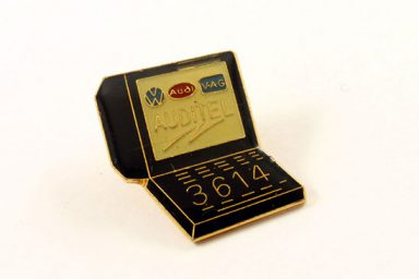 A Minitel lapel pin with the number 3614 printed on the bottom half.