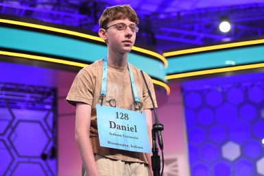 "A teenage boy with a sign around his neck that says: ""128; Daniel; Indiana University; Bloomington, Indiana"""