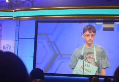 """A teenage boy, depicted on a screen, with a sign around his neck that says: """"128; Daniel; Indiana University; Bloomington, Indiana"""""""