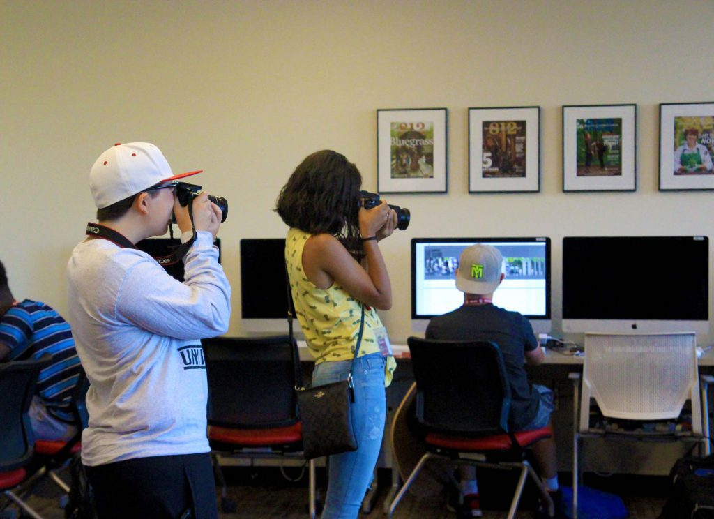 Students in a photojournalism class take photos of the different workshops.