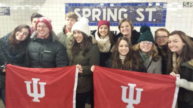 Students posing with an IU flag in a subway station