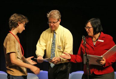 Larsen received several gifts as well as the expenses-paid trip to the Washington, D.C., area for the national bee. Scott Witzke of the School of Education and Teresa White of The Media School presented him with his awards. (Emma Knutson | The Media School)