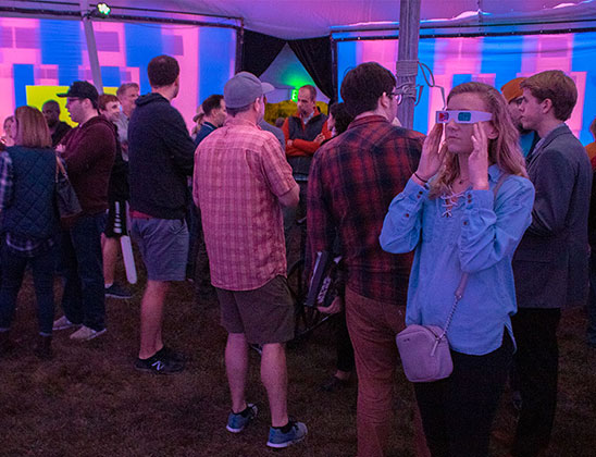 Students immerse themselves in the 12-foot-tall octagonal array of viewing screens and speaker systems at Lotus World Music and Arts Festival this weekend.