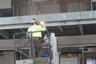 A welder works on the commons in Franklin Hall.