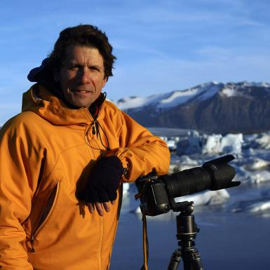 James Balog standing with a camera and tripod in front of a mountain in Iceland
