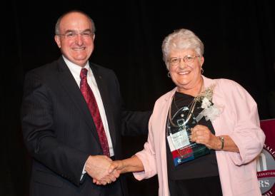 Blewett accepts the IU School of Journalism's inaugural Distinguished Alumni Award from IU president Michael McRobbie.