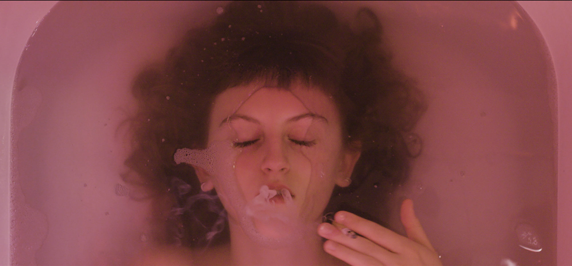 A woman lying face up in a bathtub smoking a cigarette
