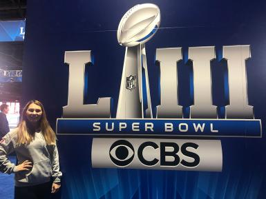 "Morgan Gard stands in front of a sign that says ""LIII Super Bowl CBS"""