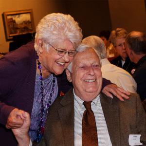 Blewett embraces journalism professor emeritus Peter Jacobi at the School of Journalism centennial celebration.