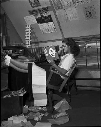 "Marjorie (Smith) Blewett reads Alfred Kinsey's ""Sexual Behavior in the Human Male"" at the Indiana Daily Student editor's desk."