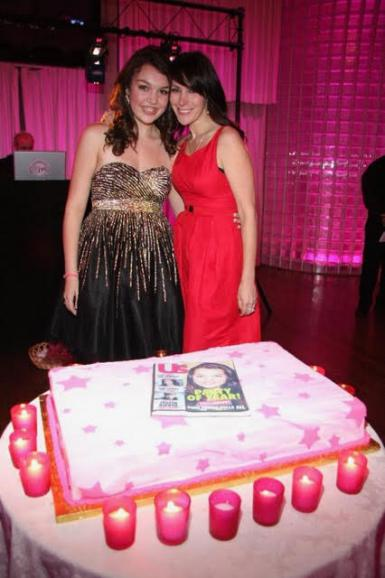 Peri Sedge and Lori Levine pose behind a cake with an image of a People magazine cover.