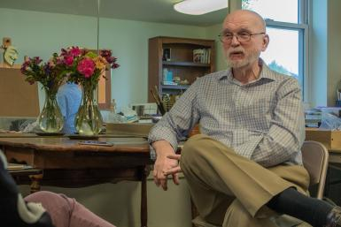 Professor emeritus Claude Cookman sits in a chair next to a table with a vase of flowers, in front of a mirror.