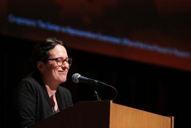 Maggie Haberman standing at a podium, smiling.