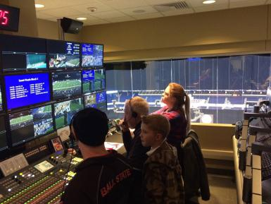 Four people watching screens in a broadcast control room at Lucas Oil Stadium