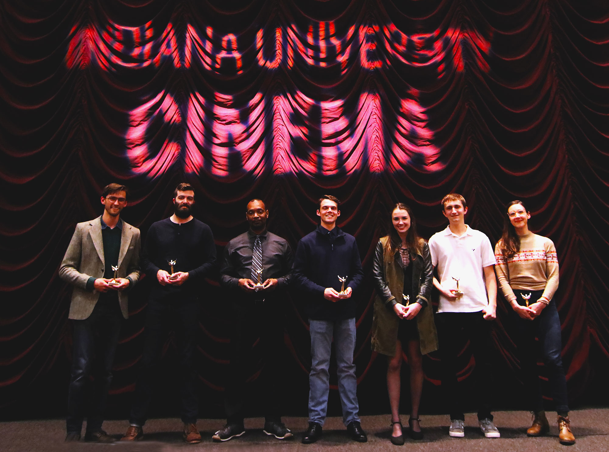 Seven students pose in front of a red theater curtain holding trophies
