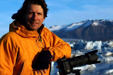 James Balog poses in front of a snowy mountain, resting his elbow on a camera on a tripod