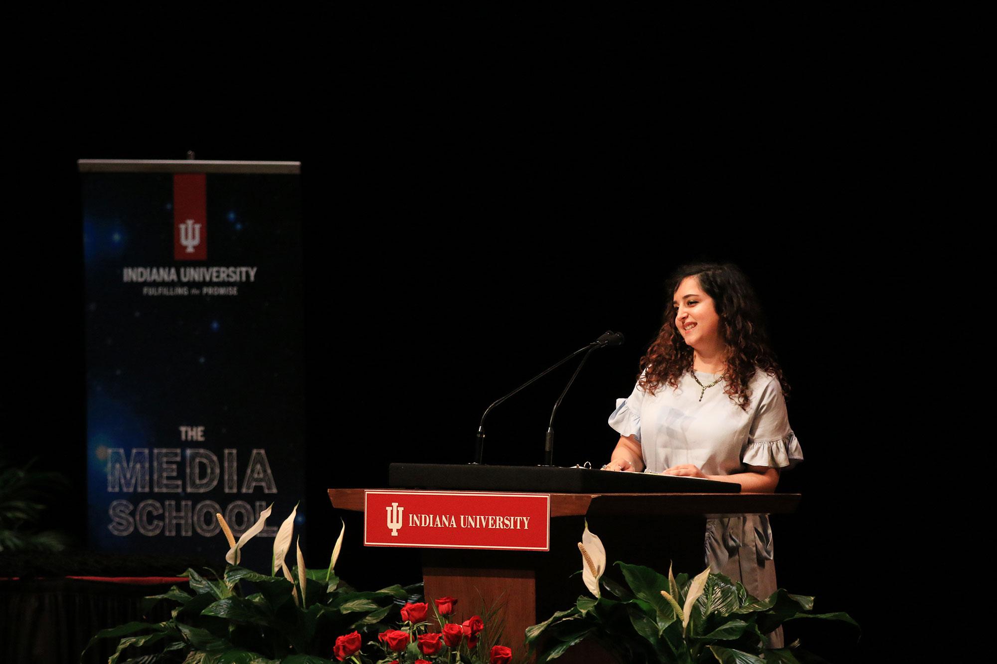 Naomi Farahan speaking at a podium