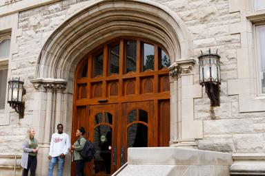 Three people stand on the entrway steps of Franklin Hall.