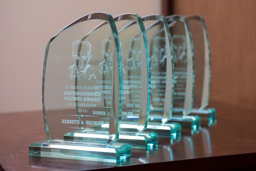 "Five Distinguished Alumni Award trophies. The first one is readable. It has an illustration of Ernie Pyle. The text reads: ""IU Media School Distinguished Alumni Award in Journalism 2016: Kenneth A. Beckley"""